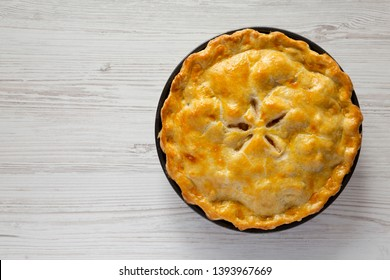 Homemade apple pie on a white wooden background, top view. Flat lay, overhead, from above. Copy space.