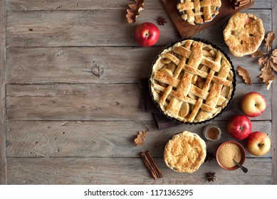 Homemade Apple Pies on rustic background, top view, copy space. Classic autumn Thanksgiving pastry dessert - organic apple pie.
