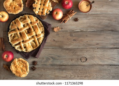 Homemade Apple Pies on rustic background, top view, copy space. Classic autumn Thanksgiving dessert - organic apple pie.