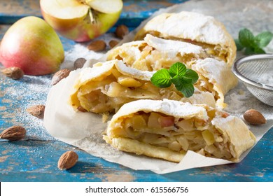 Homemade apple strudel with fresh apples, nuts and powdered sugar on a blue vintage wooden background. Country style apple strudel.