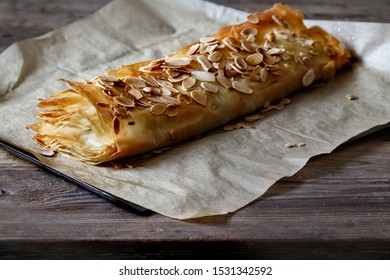 Homemade apple strudel with toasted almonds, autumn baking, fresh apples. Rustic