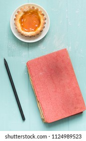 Homemade apricot cake on turquoise wooden background, with a pencil and vintage book.