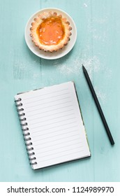 Homemade apricot cake on turquoise wooden background, with a pencil and copybook.