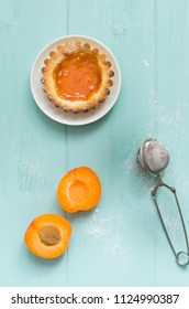 Homemade apricot cake on turquoise wooden background.