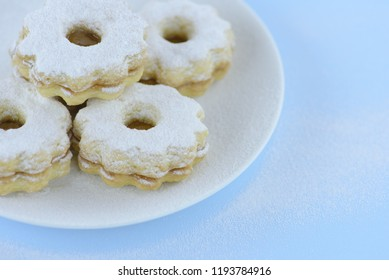 Homemade apricot jam Linzer on a white plate, pastel blue background