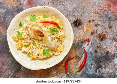 Homemade Arabian biryani overhead view on a rustic background with spices. Chicken Kabsa.
