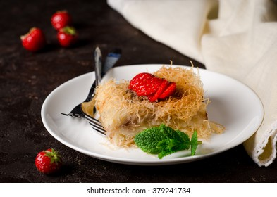 Homemade arabian traditional sweets Kunafa with strawberries and cream  in white bowl on dark stone background. Toned image. Selective focus