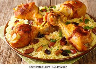 Homemade Arabic spiced rice and chicken topped with nuts, raisins closeup in the plate on the table. horizontal