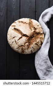 Homemade artisan bread. Freshly baked round loaf of sourdough bread with linen cloth on black background top view copy space