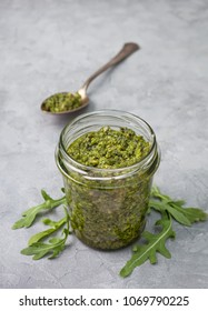 homemade arugula pesto in a glass jar on a gray concrete background. copy space