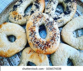 Homemade assorted bagels in a circle on a metal tray.