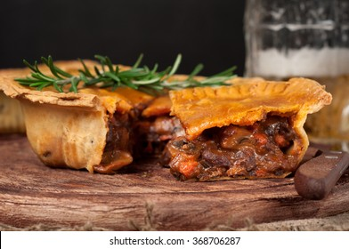 Homemade australian meat pie on the wooden table closeup with copy space, rustic style