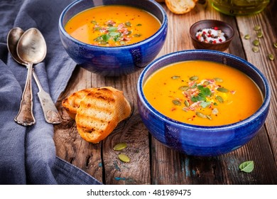 homemade autumn butternut squash soup with pumpkin seeds, bacon and basil on wooden background