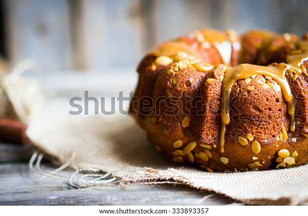 Homemade autumn cake with pumpkin seeds and caramel on wooden background