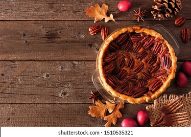 Homemade autumn pecan pie side border. Top view table scene over a rustic wood background with copy space.