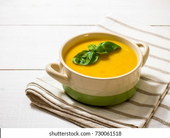 Homemade autumn pumpkin soup with basil leaf, top view