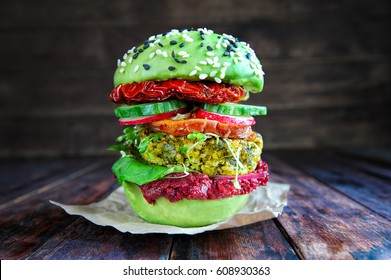 Homemade avocado burger with quinoa, sweet potato, sun dried tomatoes and beet pesto sauce