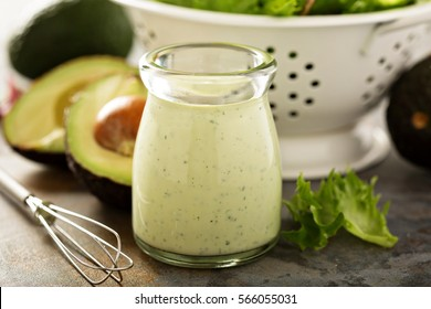Homemade avocado ranch dressing in a small jar with fresh greens.