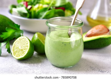 Homemade avocado yogurt dressing in a vintage glass jar with ingredients for making on a light slate, stone or concrete background.