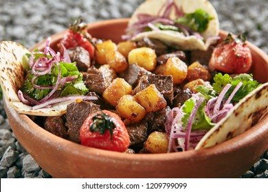 Homemade Azerbaijani Dzhiz-Byz, Jiz-Biz or Ezma with Roasted Lamb Liver, Heart and Lungs with Potatoes on Rustic Background. Grilled Offal and Vegetables with Flatbread on Natural Rustic Background