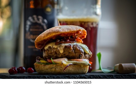 Homemade bacon cheeseburger on a dark tile with berries on the side and cold beer in the background
