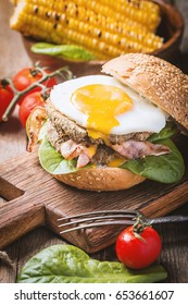 Homemade Bacon Hamburger with fried Egg, Lettuce and lentil burger with a garnish of corn and tomatoes