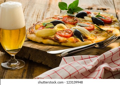 Homemade bacon pizza with tomatos onion olive basil and a glas of beer on a wood plate
