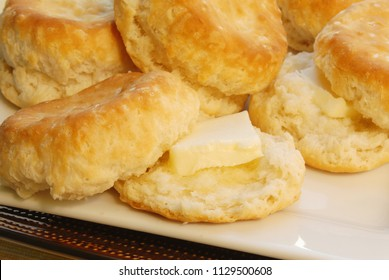 Homemade baked buttermilk biscuits smothered in melted butter served on a white plate.