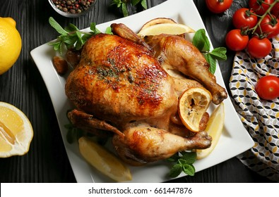 Homemade baked chicken with lemon and mint on table