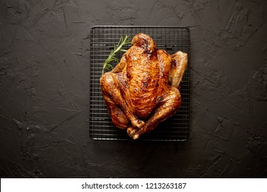 Homemade baked chicken with rosemary herbs. Served on steel black grill frame. Black stone background, Shot from above.
