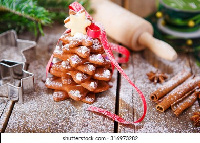 Homemade baked Christmas gingerbread tree on vintage wooden background. Anise, cinnamon, baking roll, star forms and decoration utensils. With icing sugar as snow. Selfmade gift for xmas.