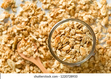 Homemade baked crunchy oatmeal, sliced almond, honey and coconut oil breakfast granola in glass jar, photographed overhead (Selective Focus, Focus on the granola in the jar)