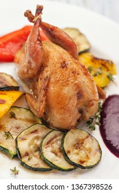 Homemade baked quails with grilled zucchini and pepper garnish and berry sauce. On a white plate. Lunch and dinner for diet. Ketogenic diet. Vertical view.
