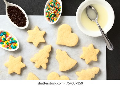 Homemade baked sugar cookies for Christmas with icing and sprinkles on the side, photographed overhead on slate