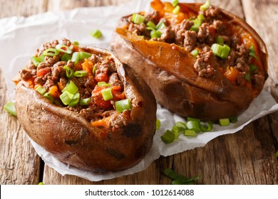 Homemade baked sweet potato stuffed with beef meat and green onions close-up on paper on the table. horizontal