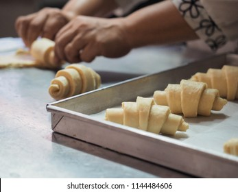 homemade baker rolling croissant dough on stainless steel table and put them on baking tray for proofing and baking.