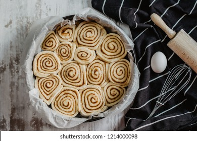Homemade baking. Cinnamon buns on the table with egg, rolling pin and whisk. Cooking concept