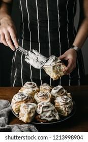 Homemade baking. Girl smears cinnamon buns with a cream