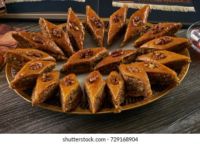 Homemade baklava or pakhlava with nuts and honey syrup on tray on wooden table background. Novruz tray with Azerbaijan national pastry, closeup. Delicious dessert holiday food