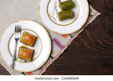 homemade baklava with pistachio and nuts, on two small plates, authentic table cloth embroderied, wooden table, space for text, feast time in muslim countries, sarma baklawa, traditional treat, saray