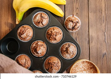 Homemade banana chocolate muffins sprinkled with sugar in a baking form on a wooden background. Top view.