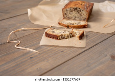 Homemade Banana Nut Bread Sliced on  Parchment Paper on Wooden Table