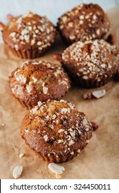 Homemade banana peanut muffins on baking paper and white wooden background