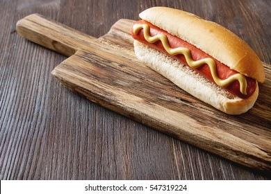 Homemade barbecue grill hotdog with mustard Yellen. fast food menu. Dark wood background.
