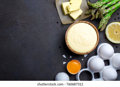 Homemade basic french sauce hollandaise in a wooden bowl with ingredients, butter, asparagus, lemon, eggs, on a black slate stone background with copy space, top view