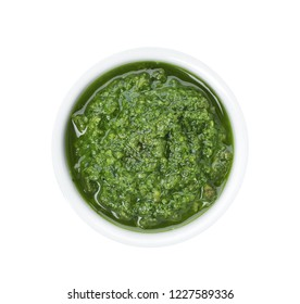 Homemade basil pesto sauce in bowl on white background