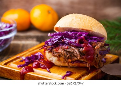 Homemade bbq beef burger with crunchy red cabbage slaw on rustic table. Barbecue meat sandwiches for christmas lunch, close up