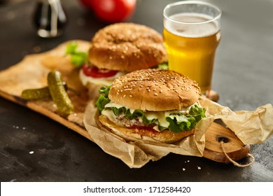 Homemade beef burgers with a glass of beer, tomatoes, cheese, sauce on wooden cutting board