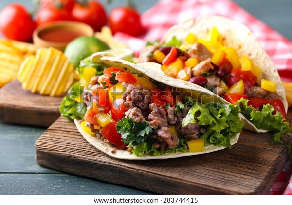 Homemade beef burritos with vegetables, potato chips on cutting board, on wooden background