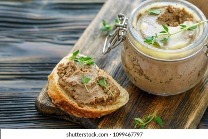 Homemade beef liver pate in a glass jar and baguette slices with pate on the serving board, selective focus.